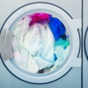 White clothes along with blue colored clothes inside a washing machine.
