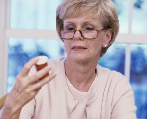 An woman wearing glasses reading a bottle.