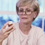 An woman wearing glasses reading a bottle.