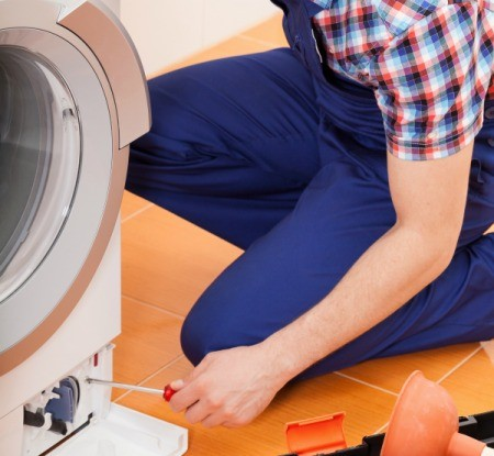 A man repairing a washing machine.