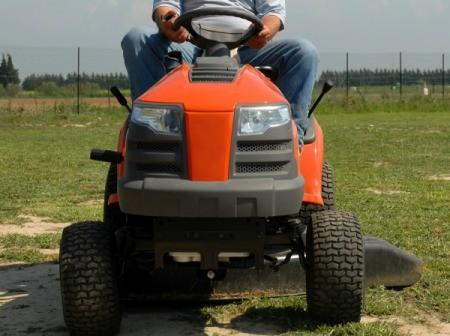 A riding mower cutting grass.