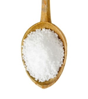 A wooden spoon full of epsom salts.