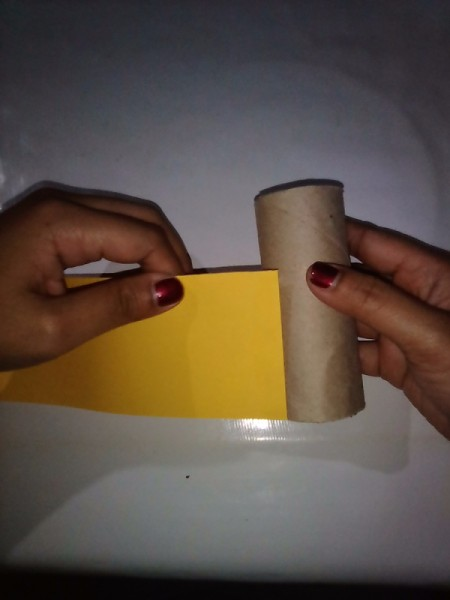 Gluing paper to an empty toilet paper tube to make the ninja's body.