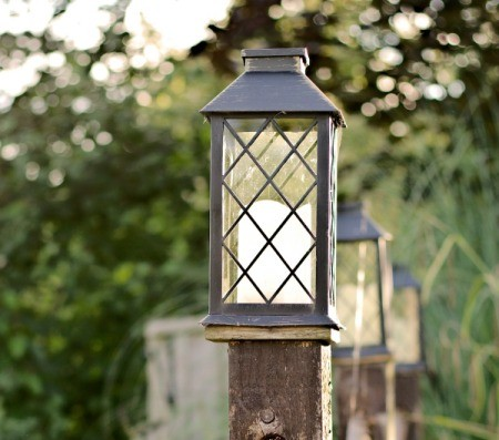 Solar lights mounted on top of fence posts.