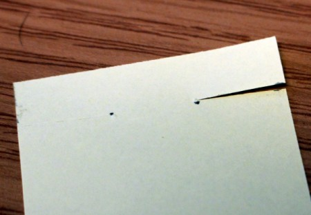 Cutting a slit to the mark on a piece of white paper.