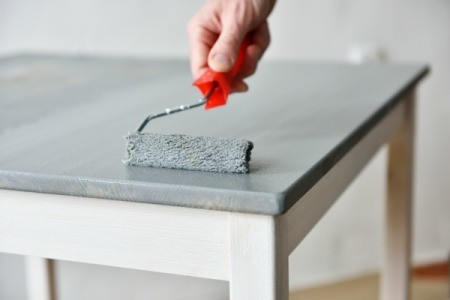 A painting a wood table using a roller.