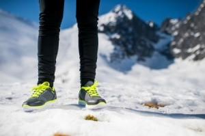 A woman wearing running shoes in the snow.