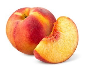 A photo of a whole peach and a peach wedge.