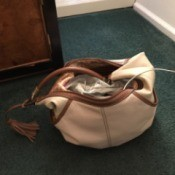 A phone inside a handbag with a phone attached to a power cord in the wall.