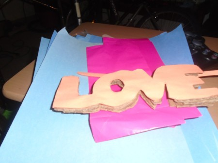 "'Love' Cardboard Sign - stack of the four words ""love"" glued together"