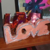 'Love' Cardboard Sign  - pink finished project displayed on a shelf