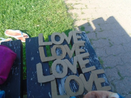 "'Love' Cardboard Sign  - four pieces of paper with the word ""love"" spelled out"