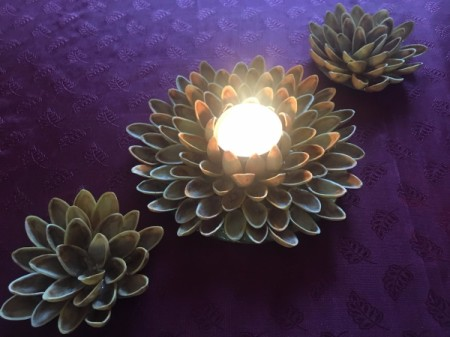 Pistachio Shell Flowers and Candle Holder - burning candle and two small flowers