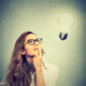 A woman in glasses looking up at a lightbulb.