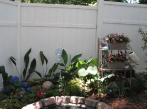 Using A Baker's Rack In Your Garden - rack near fence in garden