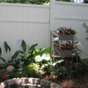 Using A Baker's Rack In Your Garden - rack near fence in garden