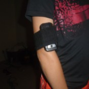 A cellphone held to an arm by the top of a black sock.