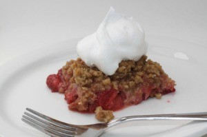 A piece of rhubarb crips topped with a whipped topping.