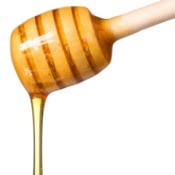 Honey dripping off of a honey dipper.