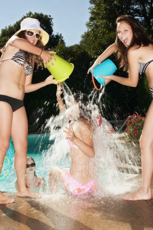 Teenage girls having fun by a swimming pool