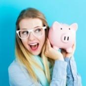 A woman holding a pink piggy bank.