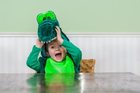 A cute kid wearing a crocodile costume.
