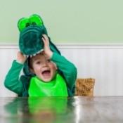 A cute kid wearing a crocodile costume.
