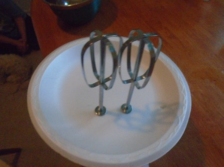 A paper plate with detachable mixers pushed through, as a splash guard.