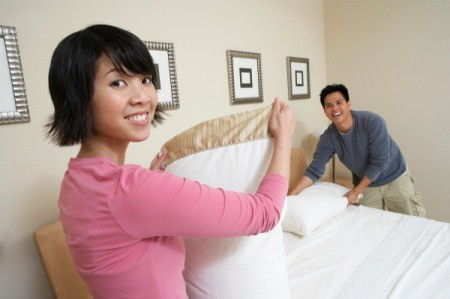 Woman Organizing a Bedroom with Her Husband