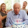 A grandfather blowing out candles at this birthday party.