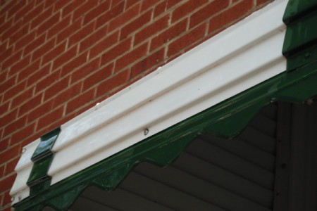 A clean section of gutter under a brick wall.