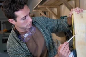 A man measuring wood.