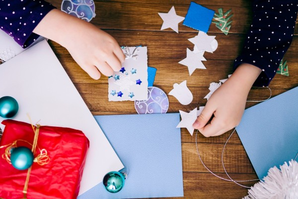 a girl making a homemade christmas card with stickers and cutouts - Homemade Christmas Cards