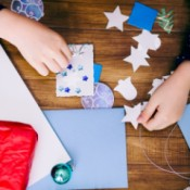 A girl making a homemade Christmas card with stickers and cutouts.