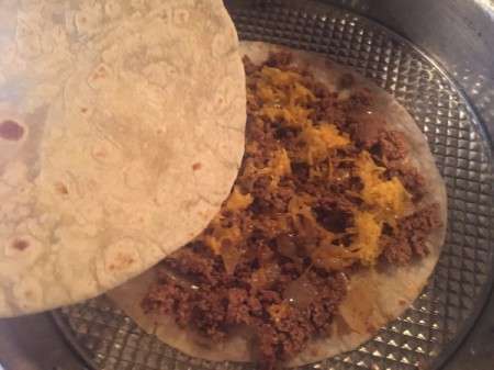 adding another tortilla to tortilla with ground beef mixture with cheese