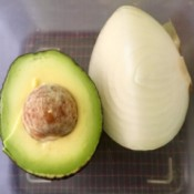 An onion stored with an avocado half.