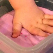 A child's hand in a container of pink flubber.