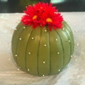 A faux cactus made from a pumpkin, pins and artificial flowers.
