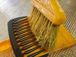 DIY Comb-top Dustpan - large tooth comb on dust pan with broom in place to clean