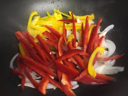 cut onions with sliced red and yellow peppers