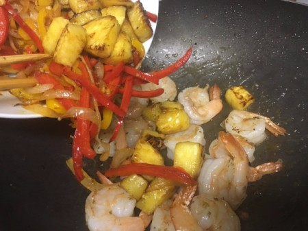 adding cooked peppers and pineapple to prawns