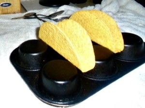 A muffin tin holding taco shells for filling.