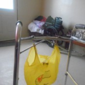 A plastic bag hanging on a walker with shower curtain hooks.