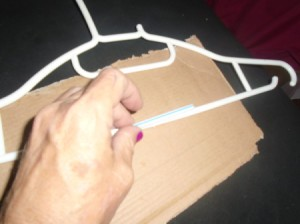A drinking straw being used to fix a broken plastic hangar.