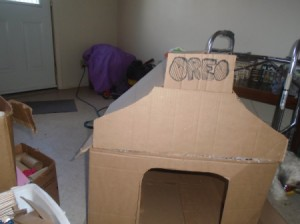 A dog house that has been constructed out of cardboard.