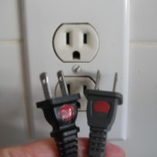 Two electrical plugs with red dots on the top side.
