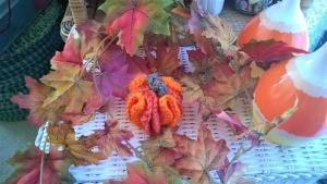Cute Little Crochet Circle Pumpkin - finished pumpkin in a bed of faux fall leaves