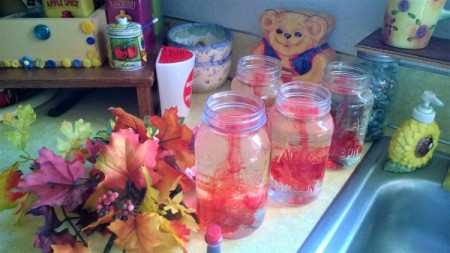 Adding food coloring to glass jars filled with water, for decoration.