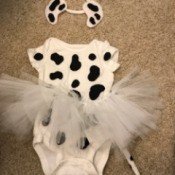A dalmation puppy costume for a baby, with a onesie, a tutu and a headband with ears.