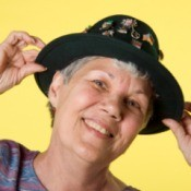 Woman with short grey hair adjusting a black hat.